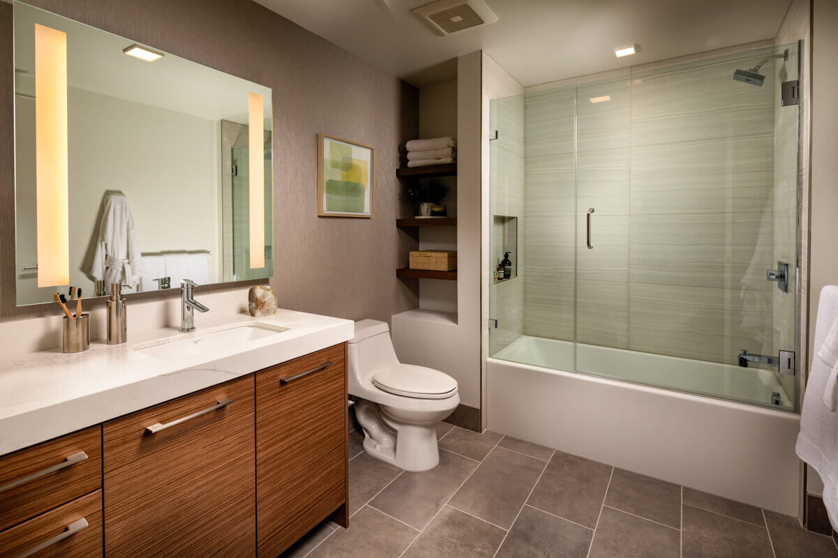 Luxury Apartments in DTLA - Park Fifth Tower Master Bathroom with Shower Tub Combo, Built-in Storage, and Porcelain Tile